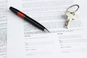 Legal document for sale of real estate with pen and house keys